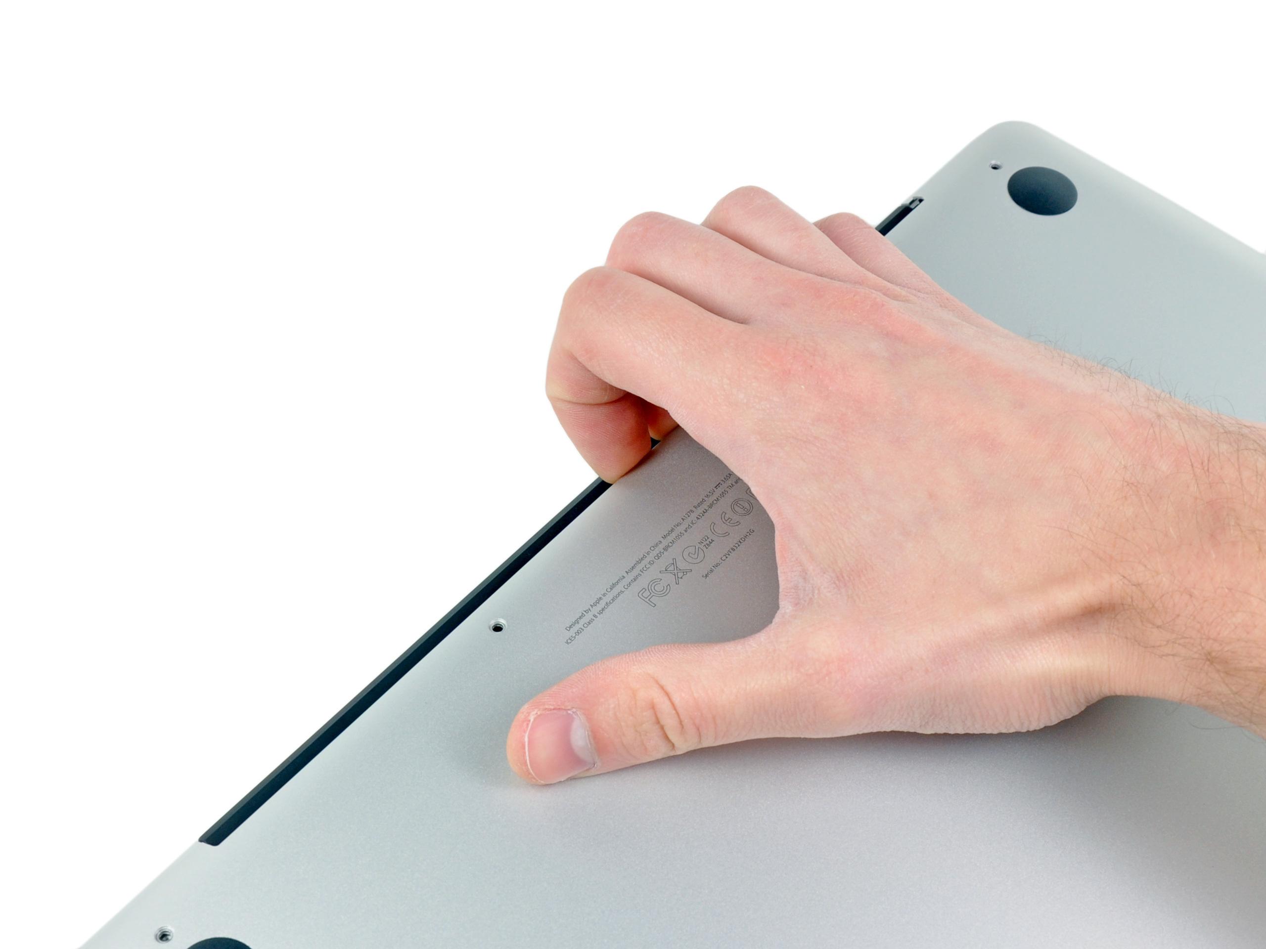 Paso 2 Use sus dedos para extraer la caja inferior del cuerpo de la MacBook cerca de la ventilación. Retire la caja inferior.